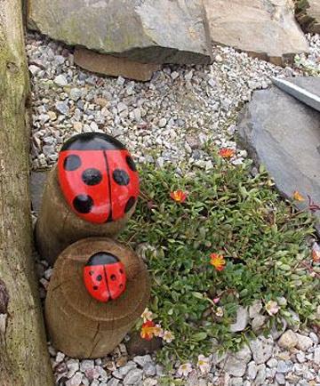 mariquitas pintadas en piedras en el jardin